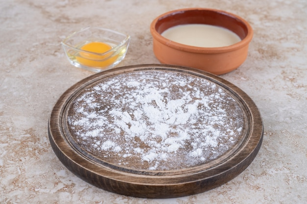 A brown plate of flour and a clay bowl
