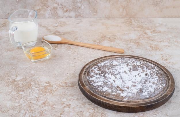 Un piatto marrone di farina e un cucchiaio di legno di zucchero