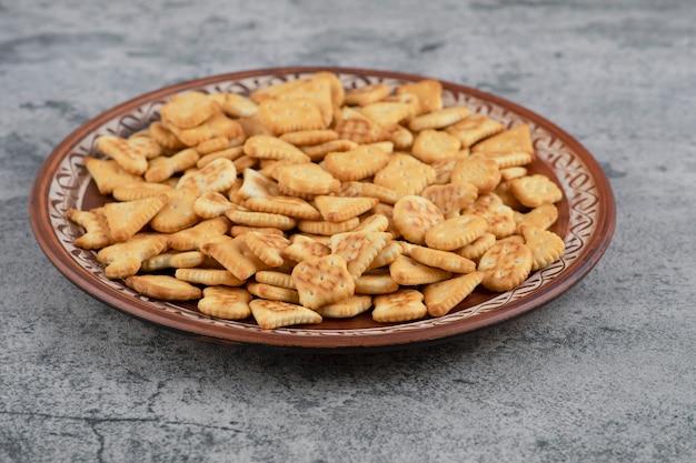 Piatto marrone pieno di cracker salati a secco su marmo.