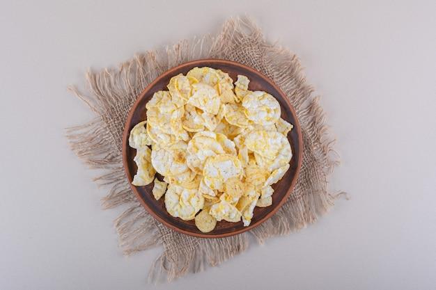 Коричневая тарелка хрустящих рисовых чипсов на белом столе