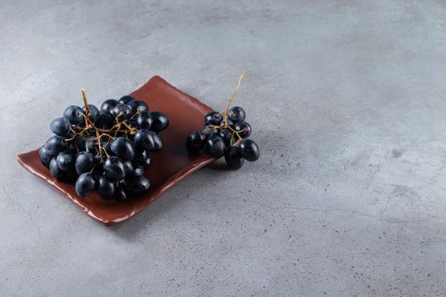 돌 배경에 신선한 검은 포도의 갈색 접시.