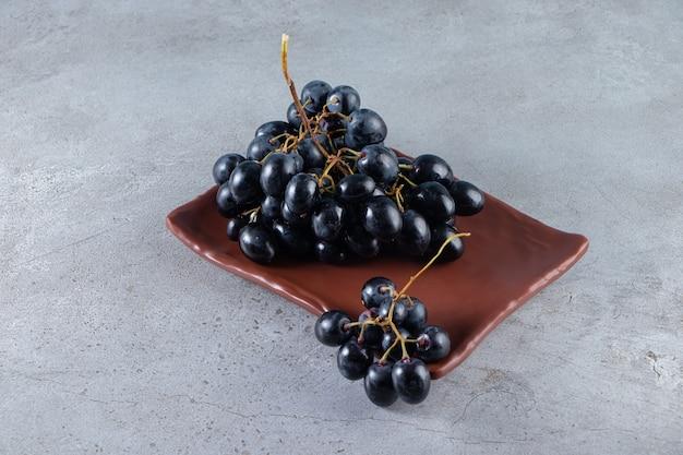 石の背景に新鮮な黒ブドウの茶色のプレート。