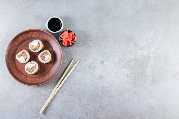 Brown plate of tasty sushi rolls with pickled ginger and soy on stone.