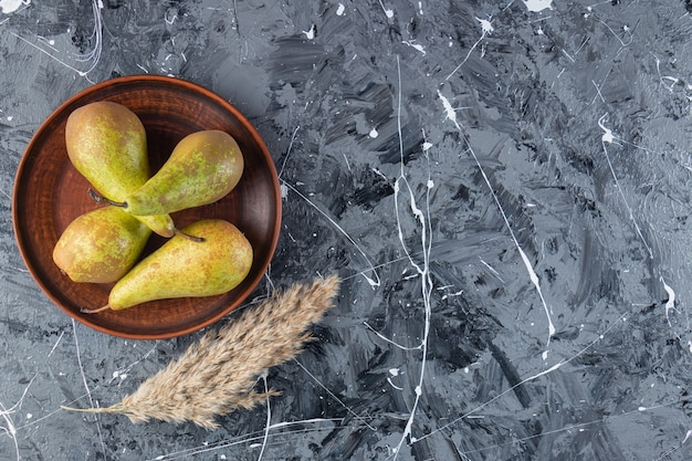 Brown plate with fresh ripe pears on marble background.