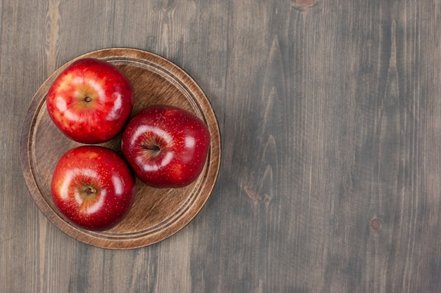 A brown plate with red juicy apples on a wooden table. high quality photo