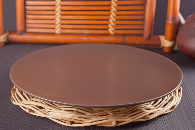 Brown plate on the wooden old table. table setting. oriental theme.