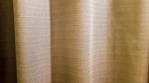 Коричневая ткань со складками. плотные, приятные на ощупь шторы крупным планом. вариант внутренней отделки. швейное изделие.