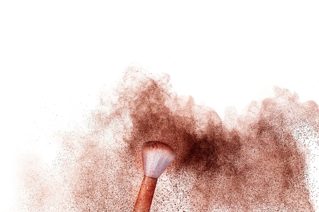 Brown powder dust cloud.brown particles splattered on white background.