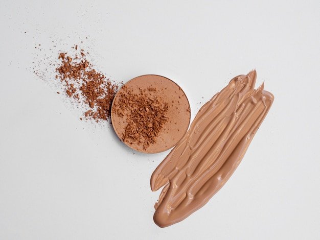 Brown powder and foundation with white background