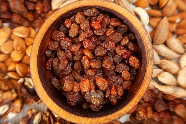Brown raisins in a wooden cedar plate on the background a scattering of various nuts.