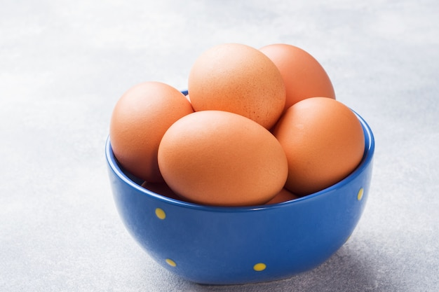 Brown raw chicken eggs in a blue bowl on a grey background.