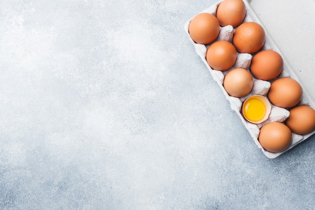Brown raw chicken eggs in factory packaging on grey background. copy space