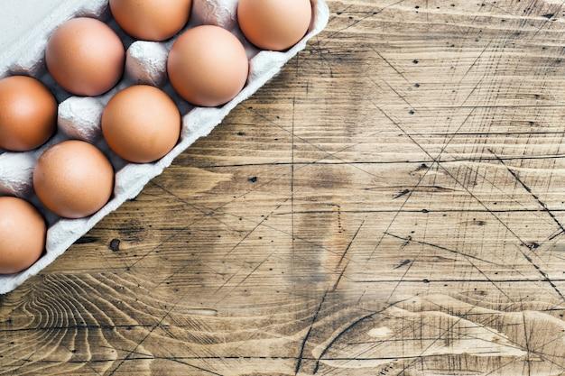 Brown raw eggs in factory packaging on rustic wooden . copyspace