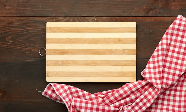 Brown rectangular wooden kitchen cutting board and red napkin
