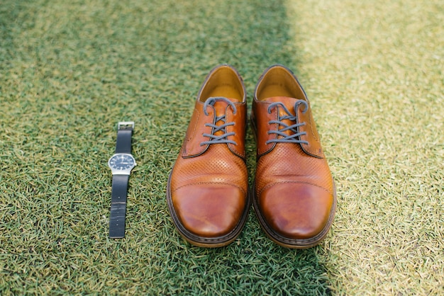 Brown red men's shoes and black wristwatch against the grass