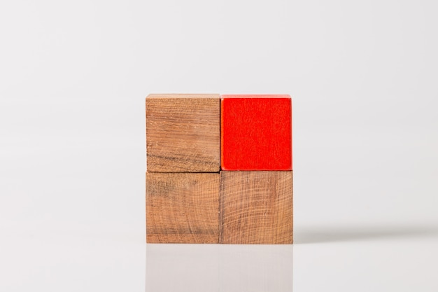 Brown and red wooden geometric shapes cube isolated on a white wall