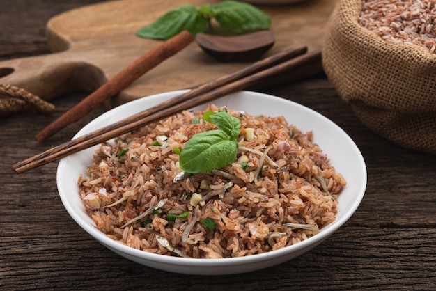 Brown rice fire with small fish on wood