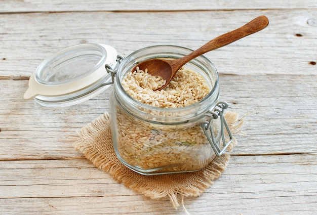 Brown rice in a glass with a spoon on wooden background
