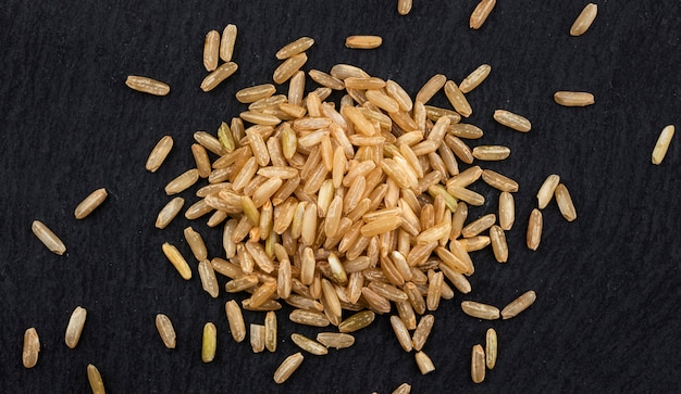 Brown rice groats on black, top view
