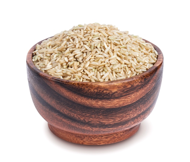 Brown rice groats in wooden bowl isolated on white background