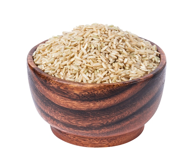 Brown rice groats in wooden bowl isolated on white