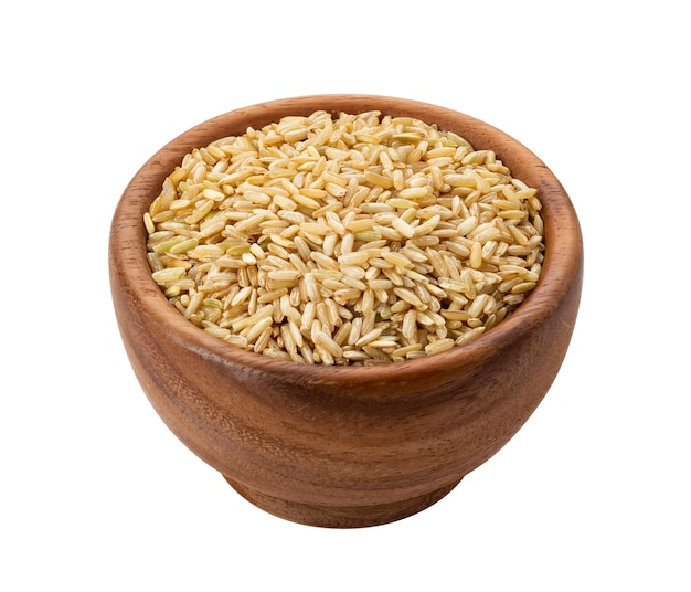 Brown rice groats in wooden bowl isolated