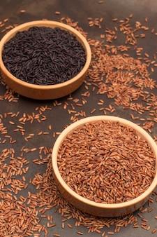 세라믹 그릇에 현미. 세라믹 그릇에 검은 쌀. 밥이 테이블에 흩어져 있습니다. 평면도