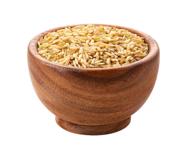 Коричневый рис в деревянной миске на белом
