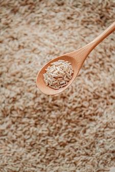 Коричневый рис в деревянной или бамбуковой ложке