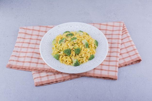 Pilaf di riso integrale con guarnizione di broccoli su fondo marmo. foto di alta qualità