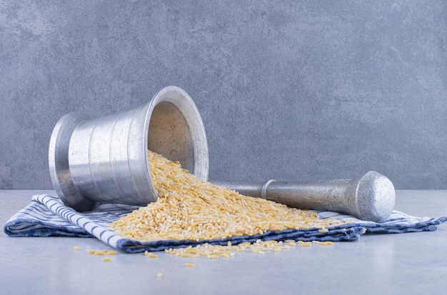 Brown rice pouring out of herb masher on a towel on marble surface