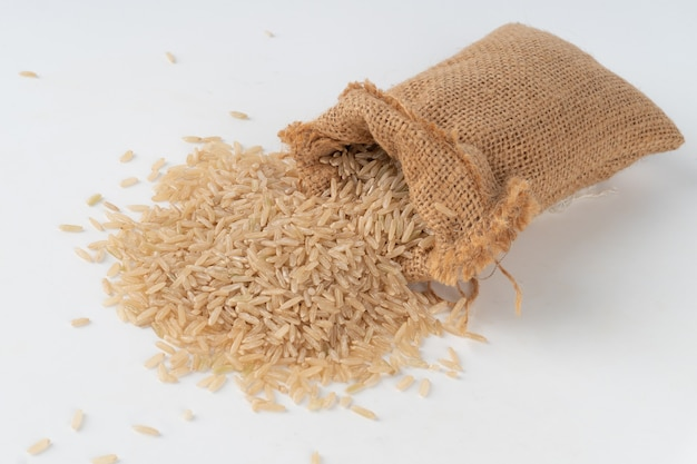 Brown rice in a sack overflowing out and scattered on the floor.