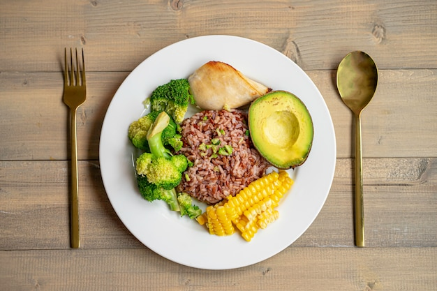 Brown rice with grilled chicken breast, boiled broccoli, sweet corn and avocado on wooden table