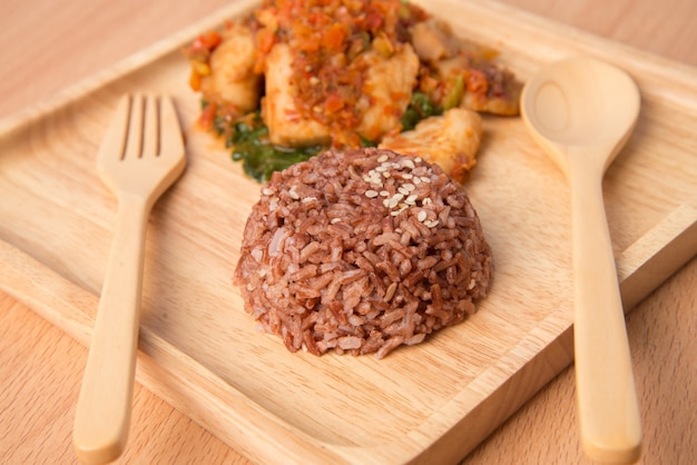 Brown rice with spicy paste stir fried with fish  in wooden dish