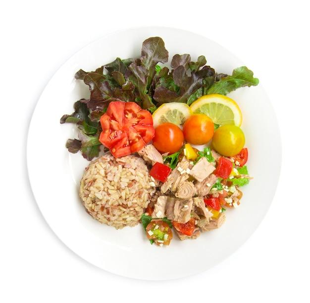 Коричневый рис с салатом из тунца прозрачный соус здоровая пища чистые продукты украшают резными помидорами, ломтиками лимона и листьями красного дуба, вид сверху на белом фоне