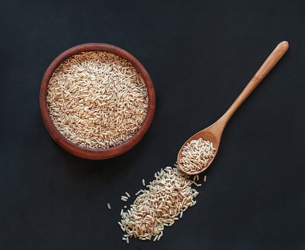 Brown rice in a wooden bowl with a wooden spoon on black background, top view