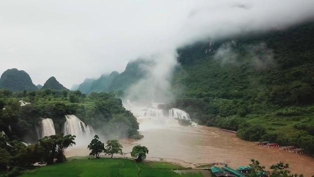 Коричневая река водопады густая растительность деревья облака горы