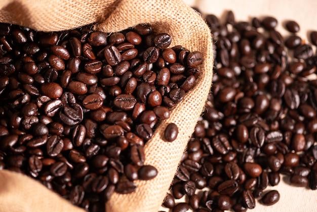 Обжаренные коричневые кофейные зерна в мешочке из ткани. жареный кофе в зернах текстуры фона
