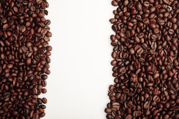 Коричневые жареные кофейные зерна, изолированные на белом фоне