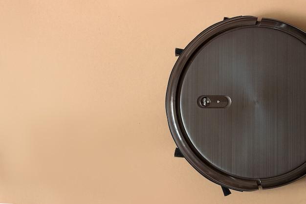 바닥에 갈색 로봇 진공 청소기. 현대적인 스마트 전자 하우스키핑 기술.실내
