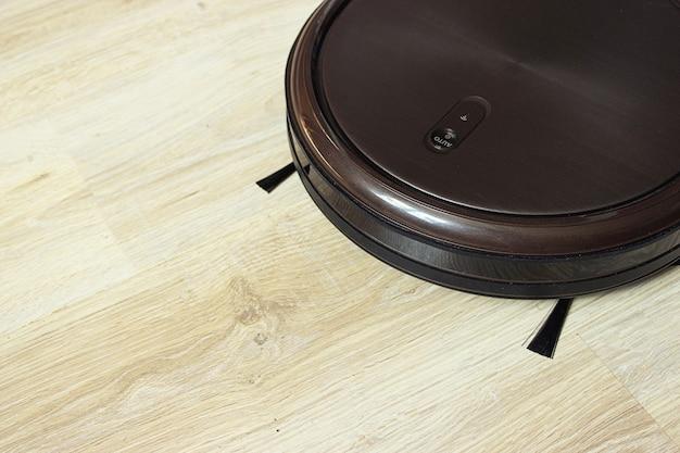 라미네이트 바닥에 갈색 로봇 진공 청소기.