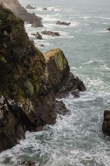 Коричневая скалистая гора у водоема в дневное время