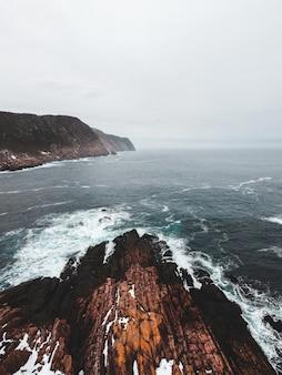 Montagna rocciosa marrone accanto al corpo d'acqua durante il giorno