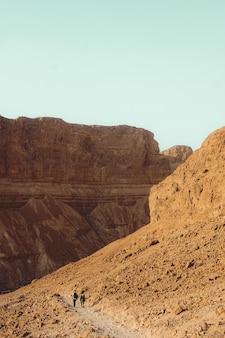 昼間の青い空の下の茶色の岩山