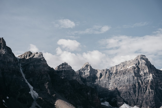 Коричневая скалистая гора под белыми облаками в дневное время