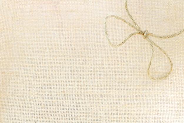 袋テクスチャ背景に茶色のロープ袋弓コピースペースがあります。