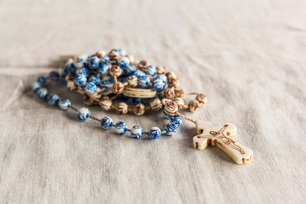 Brown rosary with blue details with image of jesus on the cross on a beige cloth
