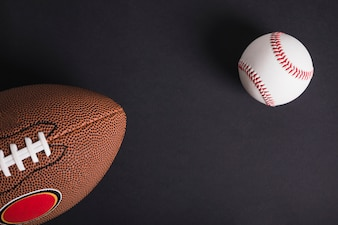 Brown rugby ball and baseball on black background