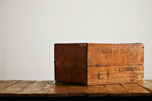 Brown rustic wooden wine box with barely legible black letters on a wooden table against white wall background