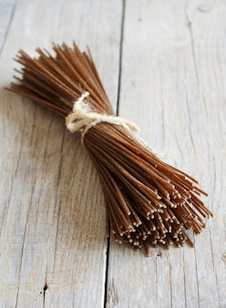 Brown rye spaghetti on the old wooden table
